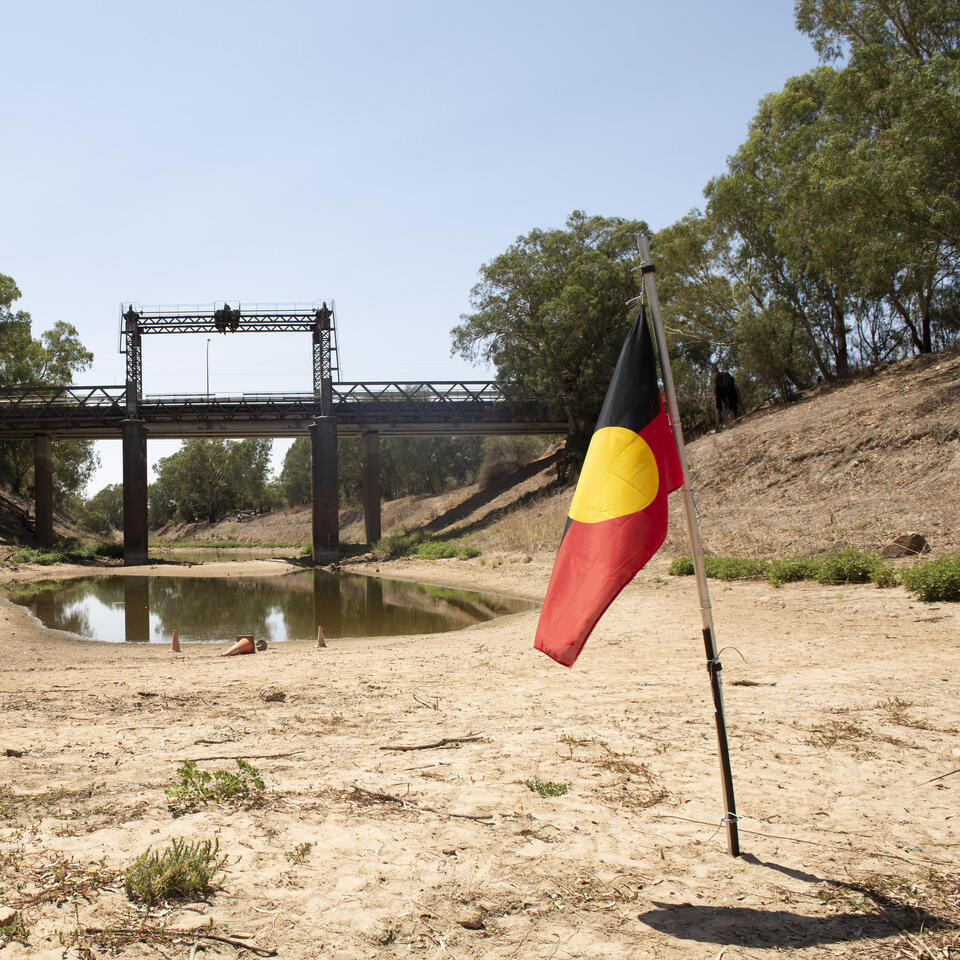 An Aboriginal flag planted on the dry riverbed of the Darling River at Wilcannia, 2019,photo by John Janson-Moore