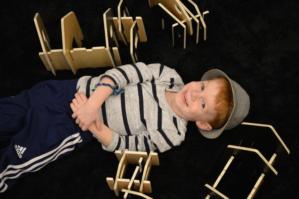 A boy making a house with wooden blocks