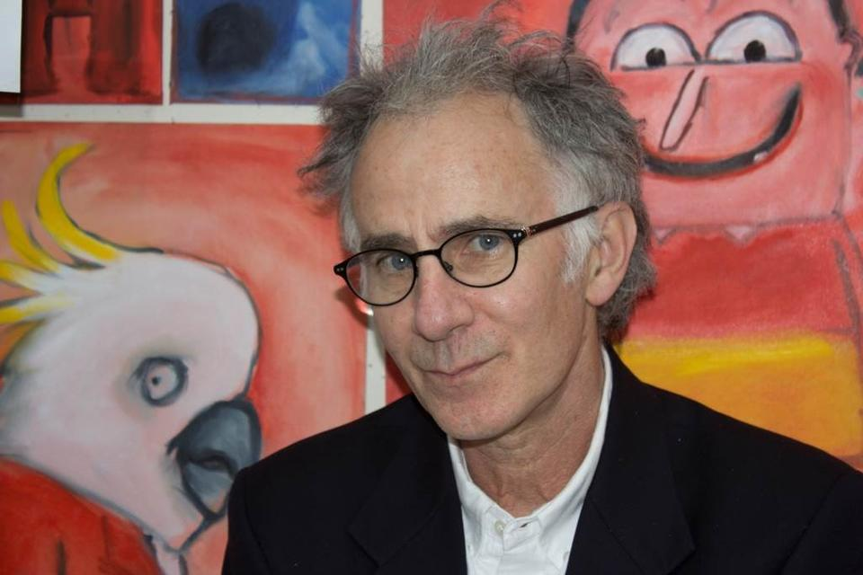man looking straight to camera with children's book illustrations in the background