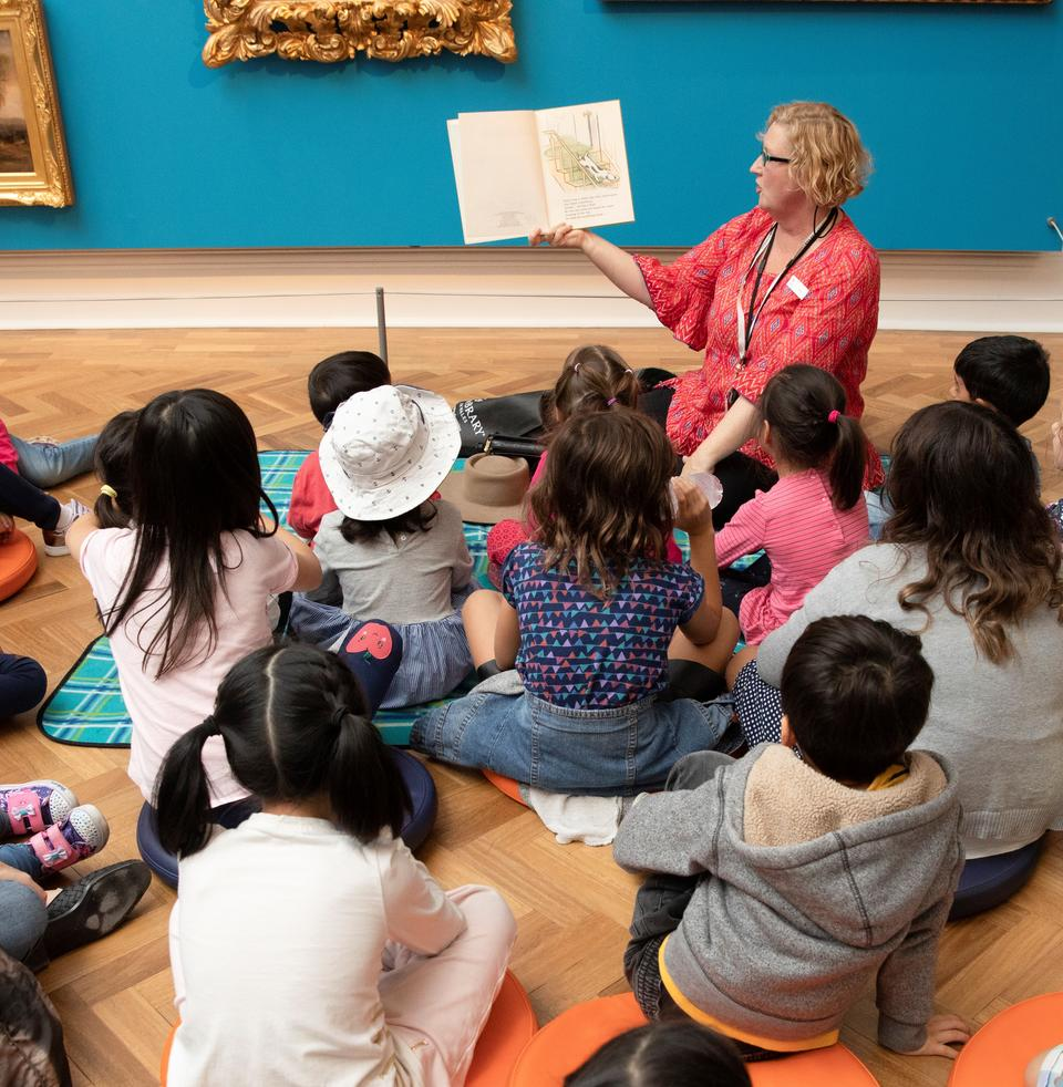 A group of children gathered around listening to a woman reading a picture book