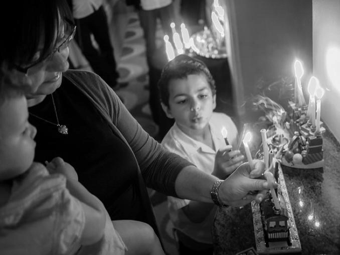 black and white image of the Slavin family lighting candles for Hanukkahh