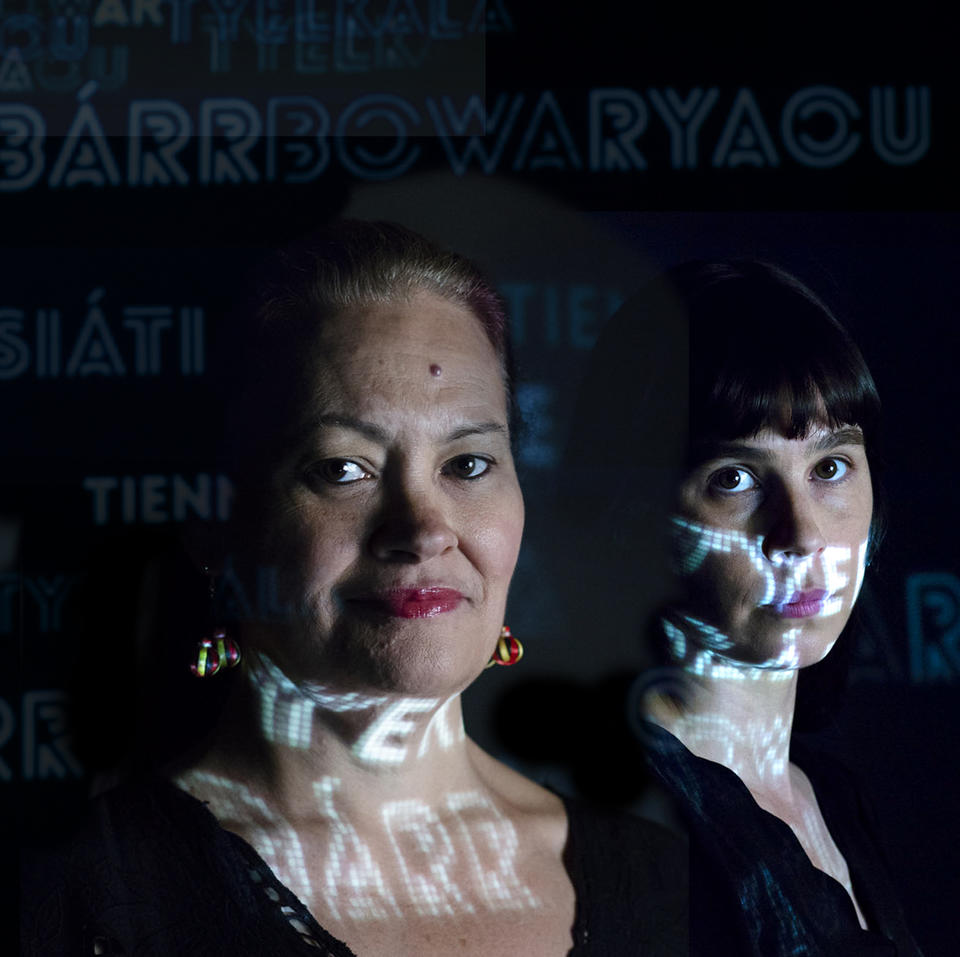 Two women, lit up by projected words.