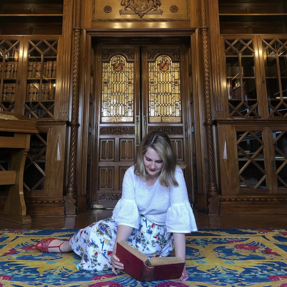 A woman reading on the floor in the Shakespeare Room.