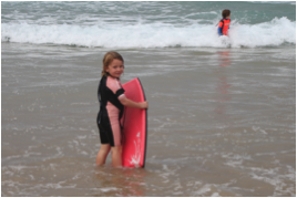 Boy in water with surfboard