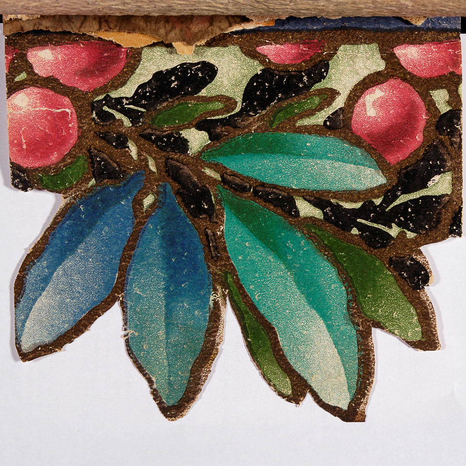 A cutout graphic of a branch with blue-green leaves and small red fruit.