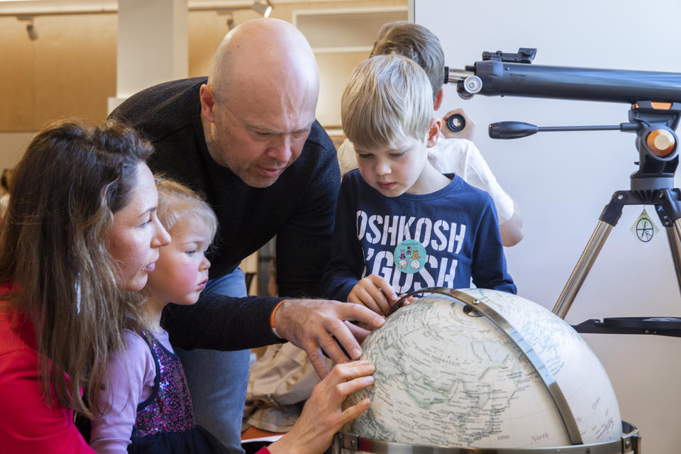 A family of four, looking and pointing at a globe