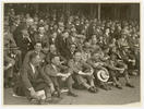 Old photo of a crowd sitting in their suits and hats attending a cricket match