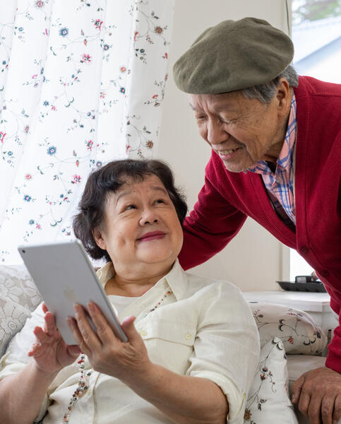 Older couple using an iPad and smiling