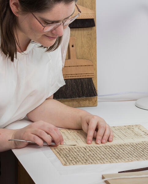 A woman conserving a hand-written manuscript