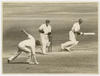 3 men in a game of cricket one running with the bat, the wicket keeper is looking at another man who missed stopping the ball