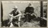Two men seated on grass on the ground wearing hats and looking down