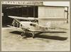 Bi plane with propellor on the ground outside an aircraft hanger