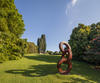 A photograph of a large metal sculpture of interlocking circles stacked vertically. The sculpture sit in a garden, with a house in the background.