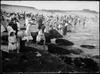 A black and white photograph of a crowded beach. Most people are fully clothed in 19th Century dress.