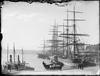 Black and white photograph of tall ships moored in a harbour.