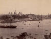 A sepia photograph of the Garden Palace taken from the north side of Sydney Harbour looking back across the harbour with tall ships in Circular Quay