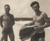 A sepia photograph of two men standing side by side on a beach, looking at the camera smiling - they wear 1930s style bathing shorts and hold towels