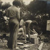 A sepia photograph of a woman washing up tin plates at a camp site - next to the camp hot plate.