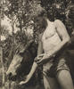 A sepia photograph of a man, wearing 30s style bathing shorts who stands feeding a horse with a crust of bread. A cigarette hangs from his lips.