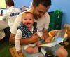 Baby sitting on lap of man looking at a book