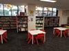 Children's area in library with tables and colourful chairs and bookshelves