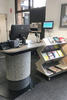 A library service desk stand, next to a shelf with wheels.