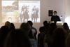 A man speaking in front of a crowd showing some images in the screen