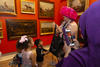 woman wearing pink hat explaining art work to a group of small children