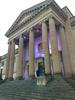 Mark Kunach, member of the Library's Inclusion Advisory Committee, stands in front of Mitchell Library buildiing lit up purple in recognition of World IBD Day