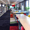 Long view of library bookshelves, tables and chairs