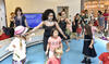 Children and adults dancing in a library with adults and other children watching
