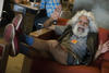A man with white hair and beard, sit on red lounge, feet up, waving and smiling at the camera.