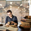 Man with glasses reading book in front of glass wall