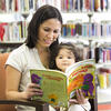 Woman reading a book to young girl - Blacktown Library