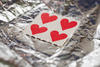Coloured tabs of paper with red love hearts sitting on aluminium foil