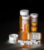 Orange pill bottles with white pills spread on black background