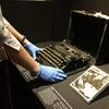Conservator Helen Casey placing conserved typewriter on display in the AMAZE Gallery for Sydney Writers Festival
