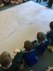 children gathered around a large map of australia