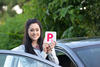 Young woman holding provisional plate next to car