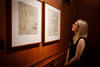 Woman looks at map on wall in State Library of NSW Map Rooms.