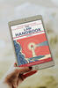 A hand holding an ipad with an image of the law handbook cover