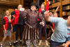 students including one in shakespearean costume jumping for joy