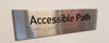 Accessible path sign with raised Braille letters
