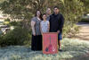 A family of four poses for the camera in front of a tree with an Aboriginal artwork.