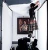 Standing on a ladder between two studio lights, a woman adjusts the lighting and environment for a painting hung on the wall behind her.