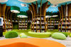 Children's library with bookshelves and seating in the design of a forest