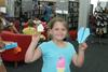 Girl smiling holding a paperplane up to the camera - Shoalhaven Library