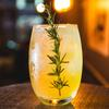 Yellow drink in a glass garnished with a sprig of rosemary
