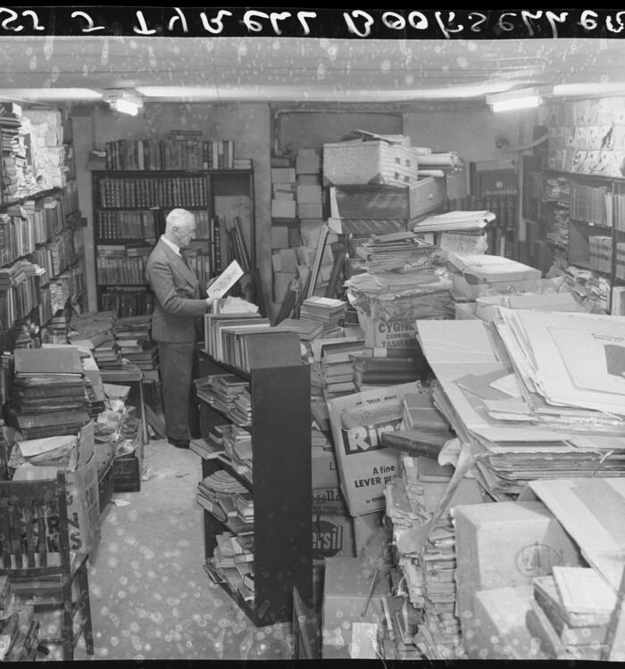 Photograph of book seller in overstocked room