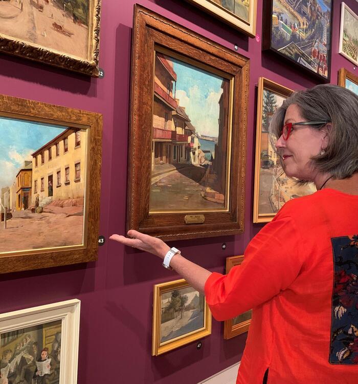woman gesturing at painting